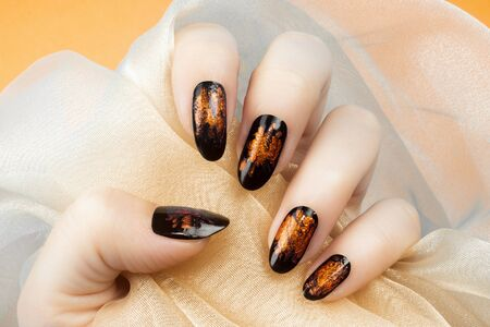 Female hand with orange black nails is holding beige textile on orange background, manicure concept.