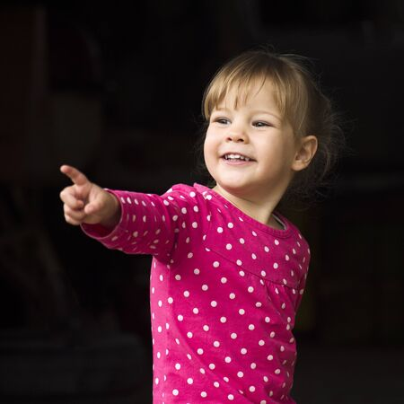 The cute little girl is showing something with her finger on black background.