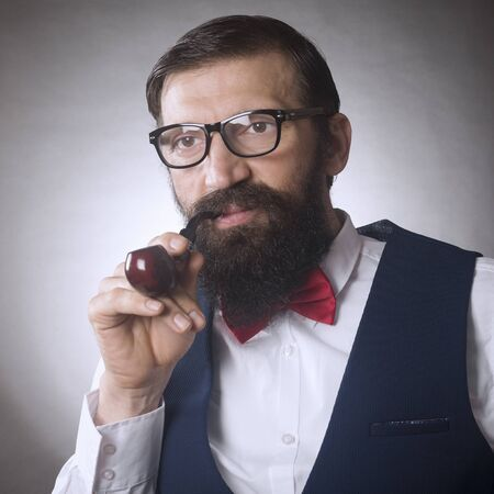 The elegant bearded hipster with eyeglasses is smoking tobacco pipe on gray background. 写真素材
