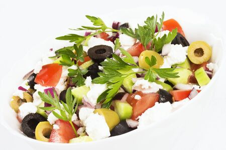 Colorful fresh Greek salad is in white dish on white background. 写真素材