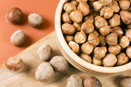 Close-up top view of whole hazelnut drupe fruit in wooden dish on cutting board.