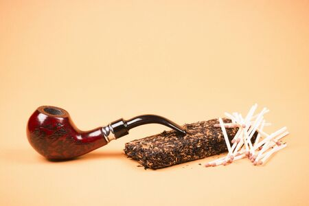 Tobacco pipe or smoking pipe, tobacco and matches on orange background, tobacco products concept. 写真素材
