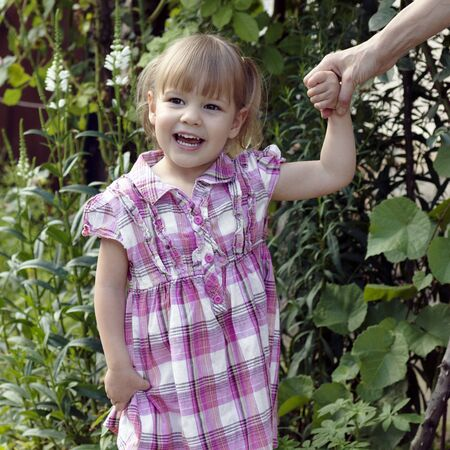 The laughing little girl in pink is holding hand of mother in garden.