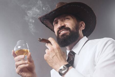 The confident bearded cowboy is smoking cigar and drinking alcohol on gray background.