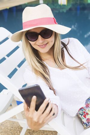 The attractive blond hair woman in hat and sunglasses is using phone.