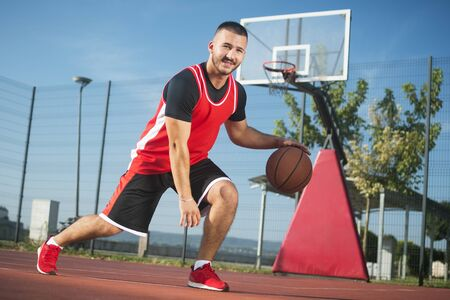 The young basketball player in red sportswear is playing streetbasket or basketball outdoors.