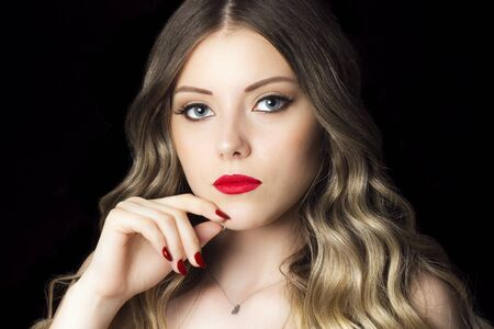 Beauty portrait of beautiful young woman with perfect face, blond hair and red lipstick on black background.