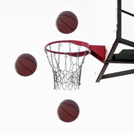 Drei Basketballbälle fliegen in die Luft zum Korb auf weißem Hintergrund, Basketballsportkonzept.