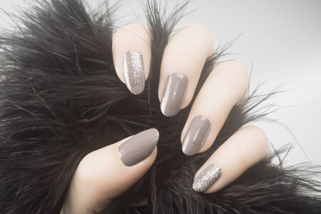 Female hand with gray nails and glittered nail polish is holding black fur on gray background, manicure concept.