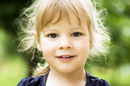 Child portrait of cute blonde little girl with disheveled messy hair on green background.