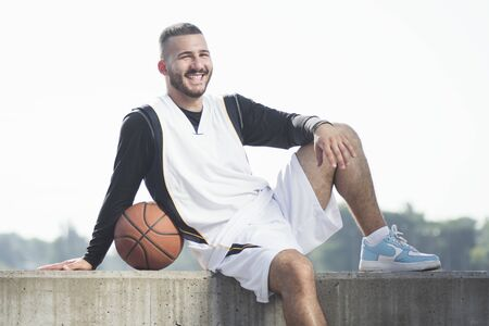 The smiling handsome young basketball player in sportswear with basketball ball is posing outdoors on white background. 写真素材