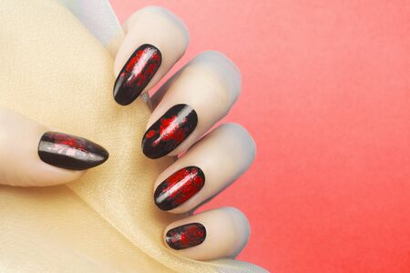 Female hand with red black nails on red background, manicure concept.