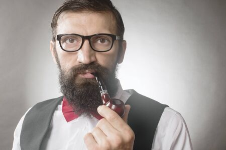 Front view portrait of bearded elegant middle aged man with eyeglasses who is smoking tobacco pipe on gray background. 写真素材