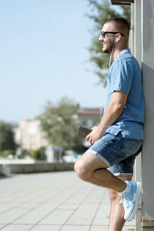 The smiling young guy with earphones is standing outdoors and using phone.