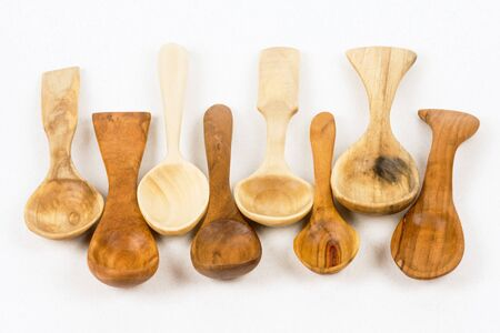Different unique wooden spoons on white background, woodcraft and wood carving concept.