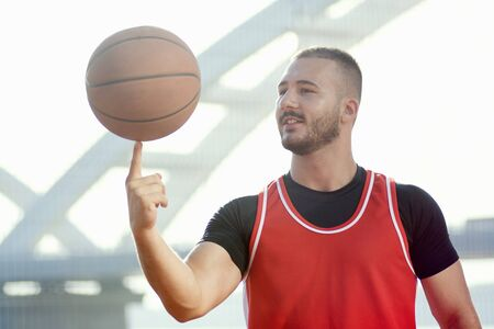 The basketball player is spinning basketball ball on finger, streetball, fun and skill concept.