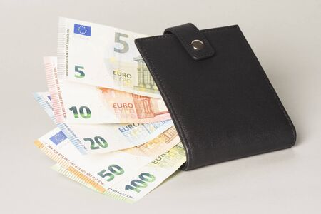 Euro banknotes are in black purse on gray background, payment and finance concept.