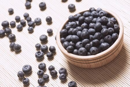Heap of blueberry berry fruit in wooden bowl on table. 写真素材