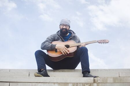 The cheerful smiling bearded man is playing guitar and sitting on stairs on sky background. 写真素材