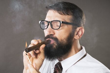 The elegant bearded man with eyeglasses is lighting a cigar on gray background.