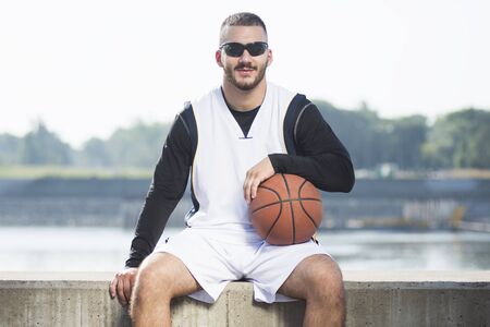 Front view portrait of cool sitting streetball or basketball player outdoors. 写真素材