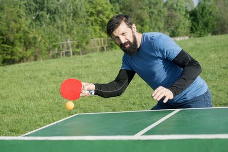 The bearded man is playing table tennis outdoors as recreation, active life concept.