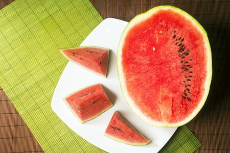 Served slices of red ripe watermelon fruit on table.