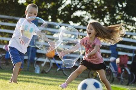 Playful happy children are playing with giant soap bubbles outdoors, cheerful childhood. 写真素材