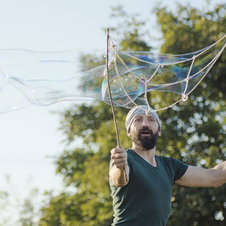 The childish playful bearded man is making giant soap bubbles outdoors.