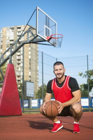 The handsome young streetbasket or basketball player is squatting on playground outdoors. 写真素材