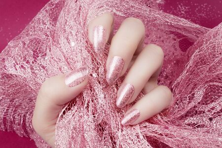 Female hand with glittered rose nails manicure is holding rose decoration on pink background. 写真素材