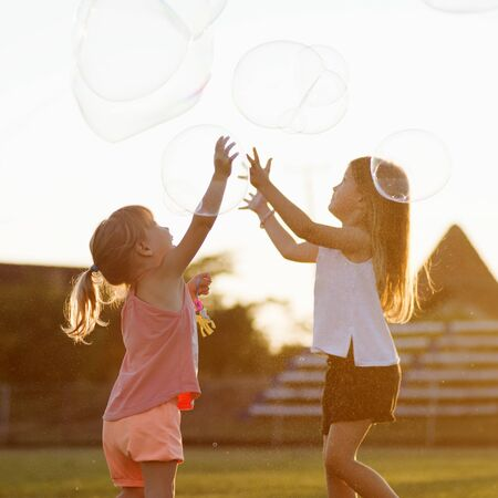 Two cheerful cute girls are playing outdoors with huge soap bubbles.