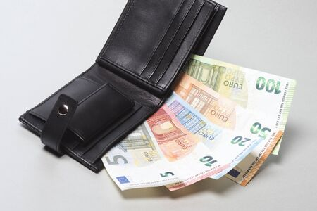 Paper currency euro banknotes are in black purse on gray background.
