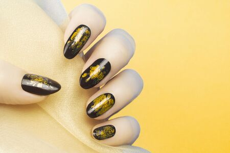 Female hand with yellow black nails on yellow background, manicure concept. 写真素材