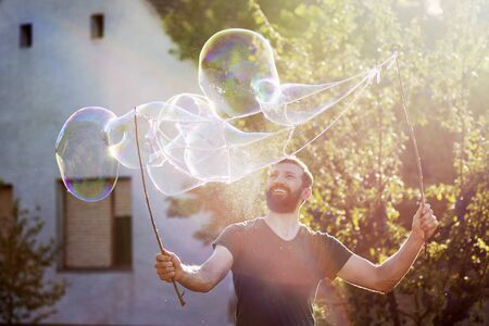 The playful bearded man is making giant soap bubbles on the street.