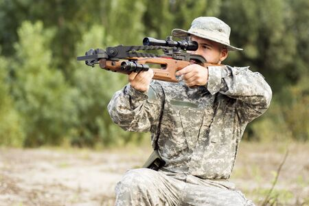 The young army soldier or hunter is aiming and shooting with crossbow weapon outdoors. 写真素材 - 129811724