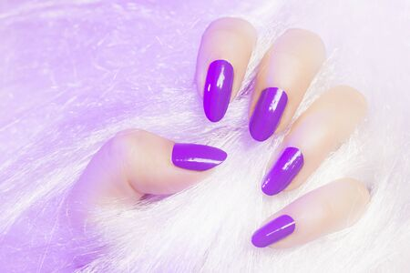 Female hand with pink nails is in white fur texture, manicure and nail care concept. 写真素材