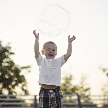 The happy cute little boy is playing with giant soap bubble outdoors on white sky background.