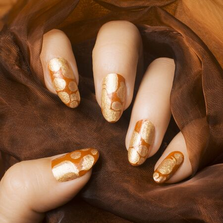 Female hand with golden and orange patterned nail polish is manicure concept.