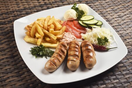 Baked sausage with french fries and different vegetables on plate is a fast food meal.