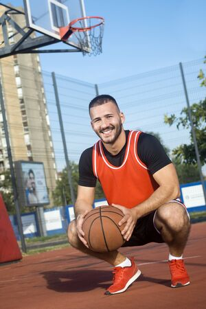 The young smiling basketball player is squatting and holding basketball ball on the playground outdoors.