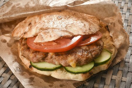 Fast food meal or street food, hamburger or pljeskavica with pork meat, cucumber and tomato. 写真素材