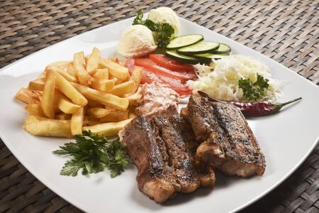 Fast food meal from baked bacon or steak with french fries and raw vegetables garnish.