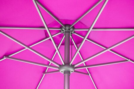 Close-up and geometric star shapes of pink parasol or under umbrella.
