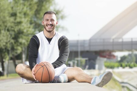 The young handsome smiling basketball player is sitting and resting with basketball ball outdoors.