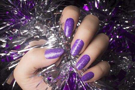 Female hand with glittered purple nails is holding decoration, manicure and nail care concept. 写真素材