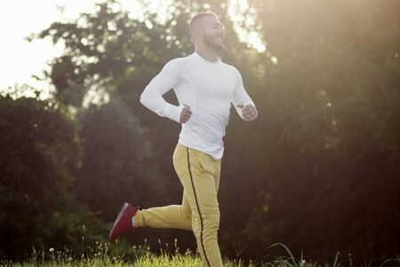 The sporty young guy is jogging or running outdoors in nature, recreation concept.