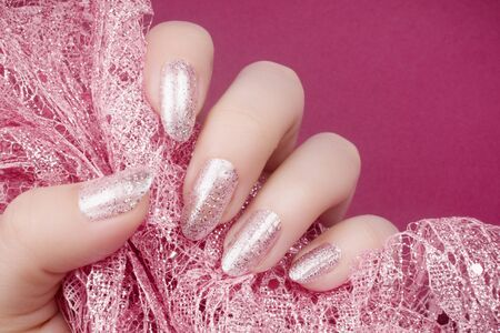 Female hand with glittered shiny rose colored nails is holding decoration, manicure and nail care concept.