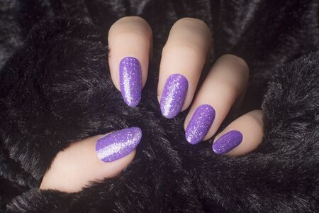 Female hand with glittered purple nails is holding black fur, manicure and nail care concept. 写真素材