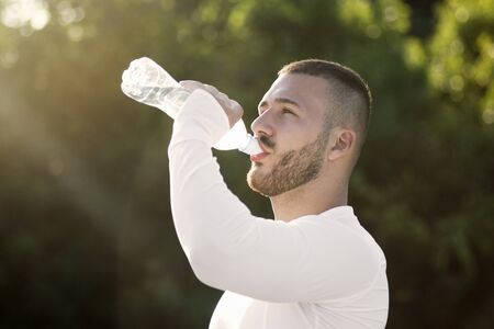 The sporty young guy is drinking water from bottle for hydrating outdoors in nature after recreation.